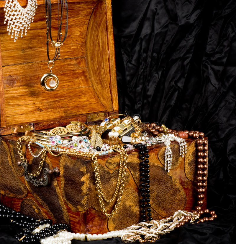 Wooden open chest with golden jewelry stock photography