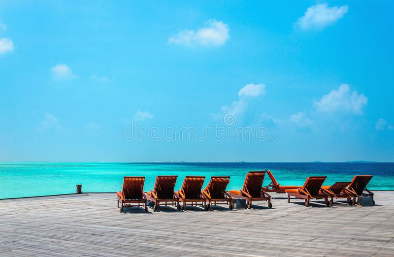 Wooden orange deck chairs on a pier on the background of the azure water, Indian Ocean, Maldives stock photos