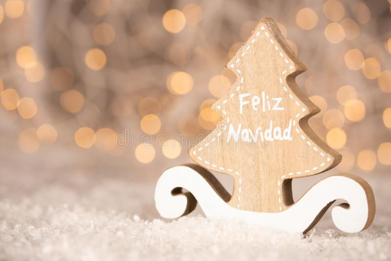 Wooden ornament cutout in the shape of a pine tree with copy space - translation text Feliz Navidad - merry christmas. Wooden ornament cutout in the shape of a royalty free stock photo