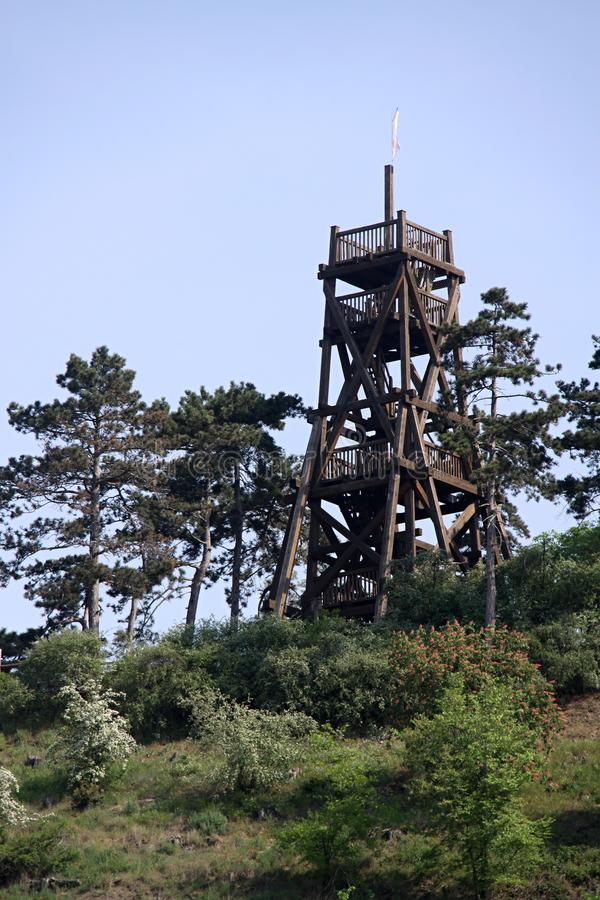 Wooden outlook tower on the top of the hill. Wooden outlook tower above the trees on the top of the hill stock photography