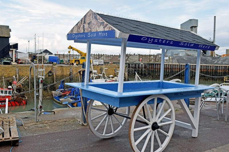 A traditional oyster cart. A wooden oyster cart that is used to push around by people to sell fresh oyster that they have caught in the Kent town of Whitstable royalty free stock photography