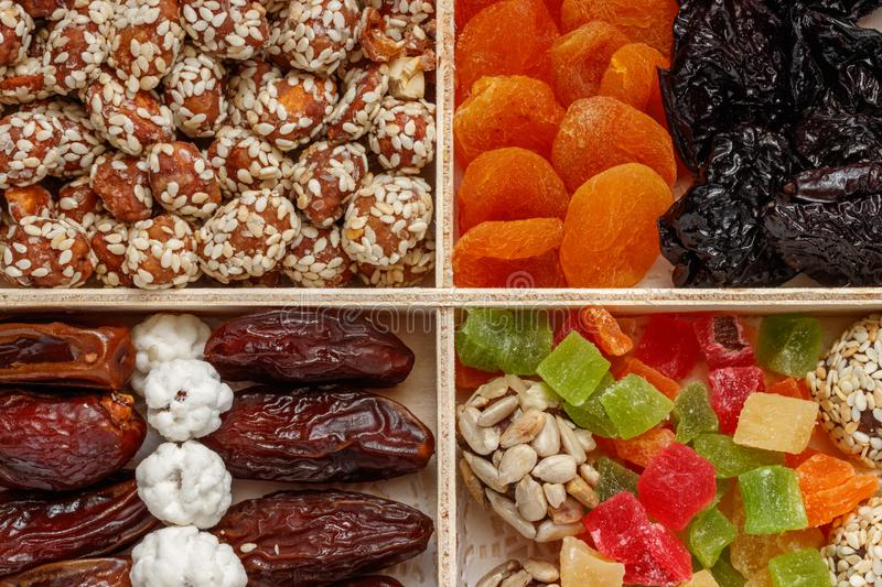 In the wooden package is dried apricots, peanuts, sesame, dried fruits, kumquat, plum stock images
