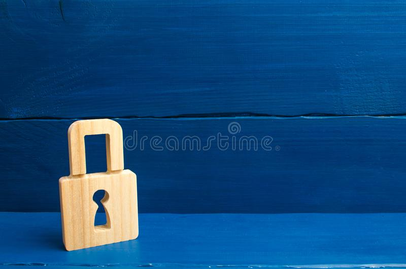 A wooden padlock on a blue background, information, entrance. Wooden figures of persons carry guards from wicked men, spies. conce. Pt of the preservation of stock photo