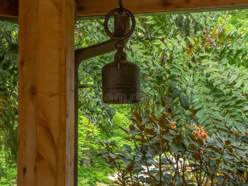 Wooden pagoda in garden setting with bell hanging from beam stock photos