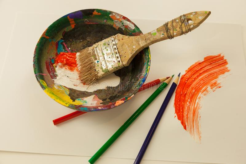 Wooden paint mixing bowl white and orange wet paint smeared Large paintbrush map coloring pencils stock photography