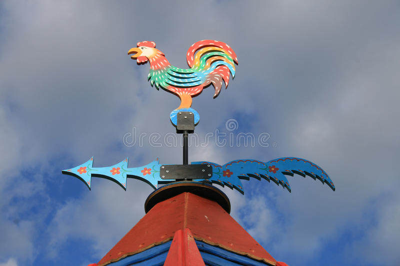 Wooden painted vane. The figure of a rooster and the wind direction indicator, Russia stock photography