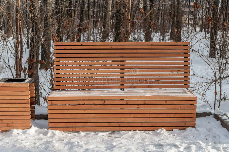 A wooden painted yellow color beautiful bench with white snow and a basket in a park in winter in a sunny day royalty free stock images