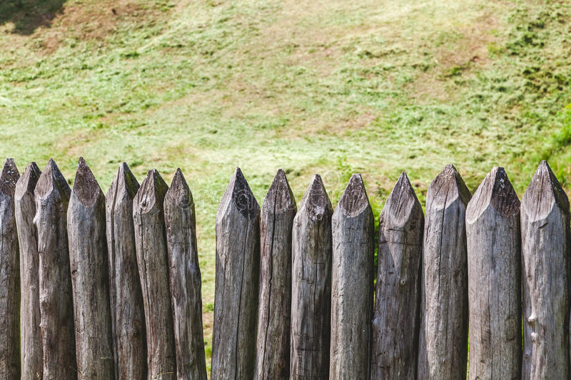 Wooden palisade of sharpened logs. Summer day stock photos