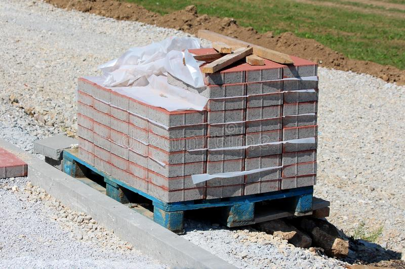 Wooden pallet partially stacked with grey and red rectangle stone tiles covered with nylon protection left next to gravel sidewalk. Surrounded with gravel and royalty free stock photography