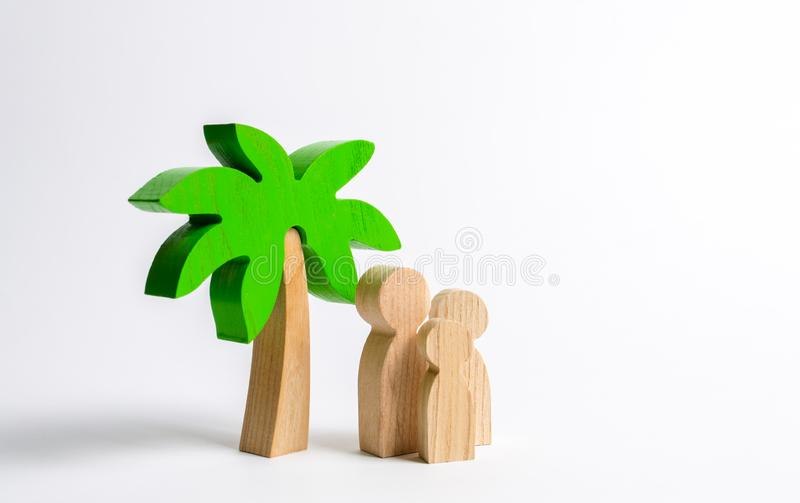Wooden palm tree and family. Family holidays with children. Tours and cruises to warm countries. The development of tourism. stock images