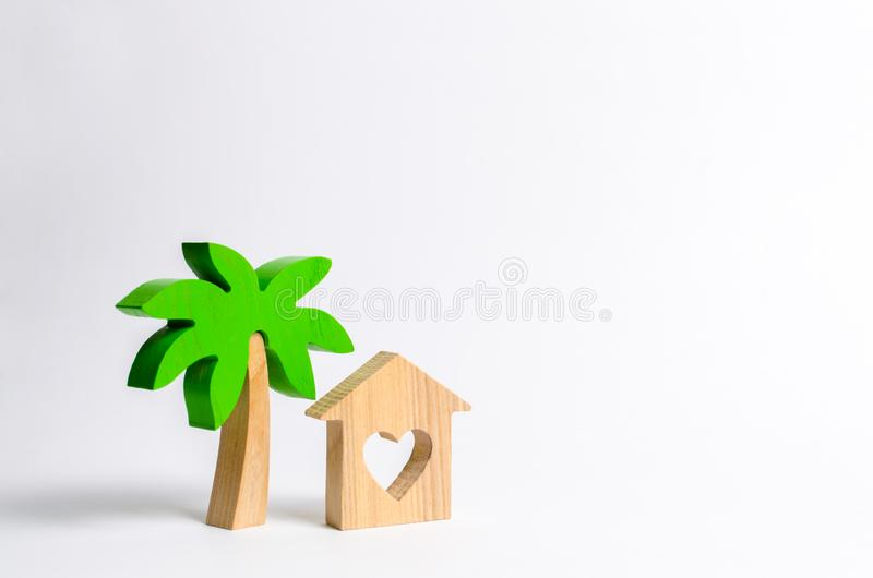 Wooden palm tree and house with hearts on a white background. Conceptual leisure and vacation. Rental homes and properties in the stock images