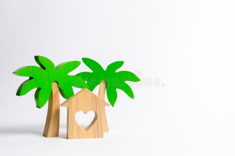 Wooden palm tree and house with hearts on a white background. Rental homes and properties in the resort. Romantic travel. royalty free stock images