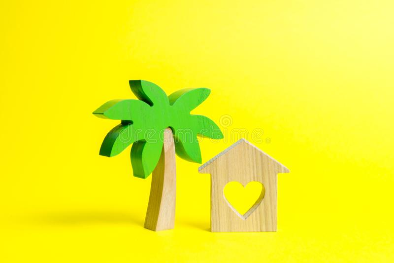 Wooden palm tree and house with hearts on an yellow background. Rental homes and properties in the resort. Romantic travel royalty free stock photos