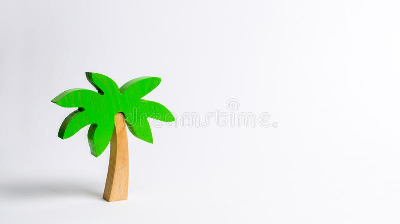 Wooden palm tree on a white background. Conceptual leisure and vacation, entertainment and relaxation. Tours and cruises to warm royalty free stock image