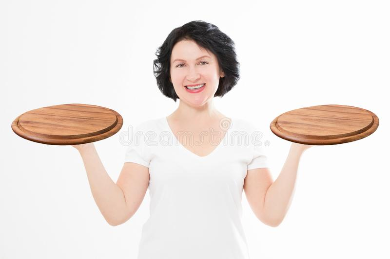 Wooden pan. Middle age attractive woman in summer tshirt holding empty pizza tray isolated on white background. Copy space stock photography