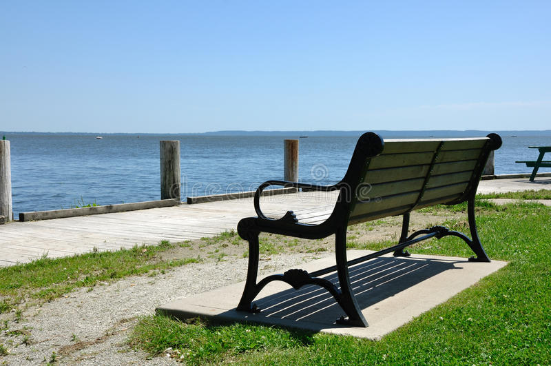 Wooden Park Bench. By a Lake on a Sunny Day stock photography