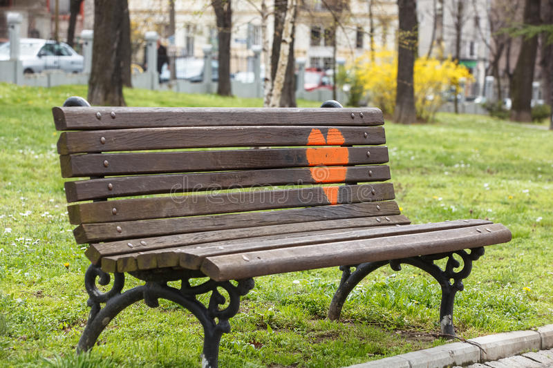 Wooden park bench at a park with red heart painted on it. In spring stock photos