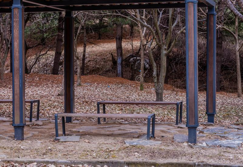Wooden park benches in January. Wooden park benches under a wooden awning with ground of boulders in a woodland park in January royalty free stock photo