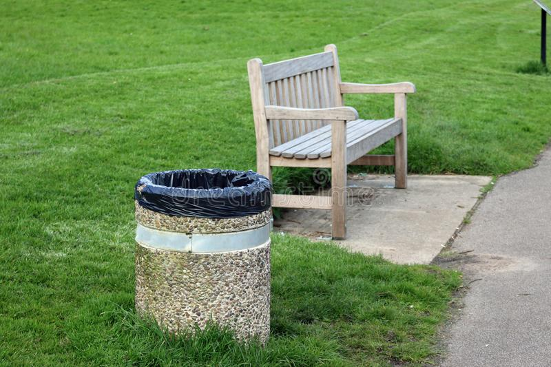 Wooden seat with concrete litter bin. Wooden park seat on a concrete plinth with an adjacent concrete litter bin containing a black plastic bin liner with grass stock photos