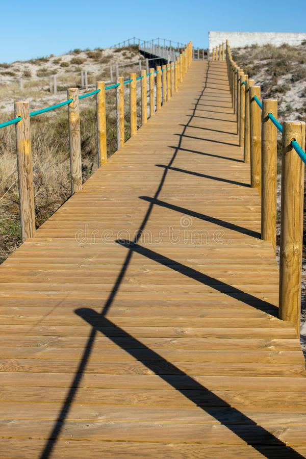 Wooden path with fence to the beach. Walkway on seashore in the morning. Atlantic Ocean coast in Portugal. Wooden path with fence to the beach. Walkway on royalty free stock photos
