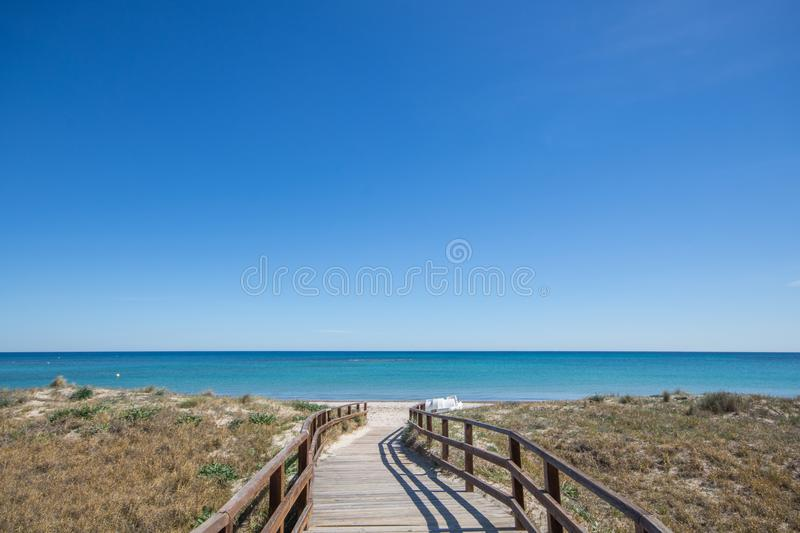 Wooden path leading to sandy beach and clear blue water with clear sky on a sunny summer day royalty free stock images