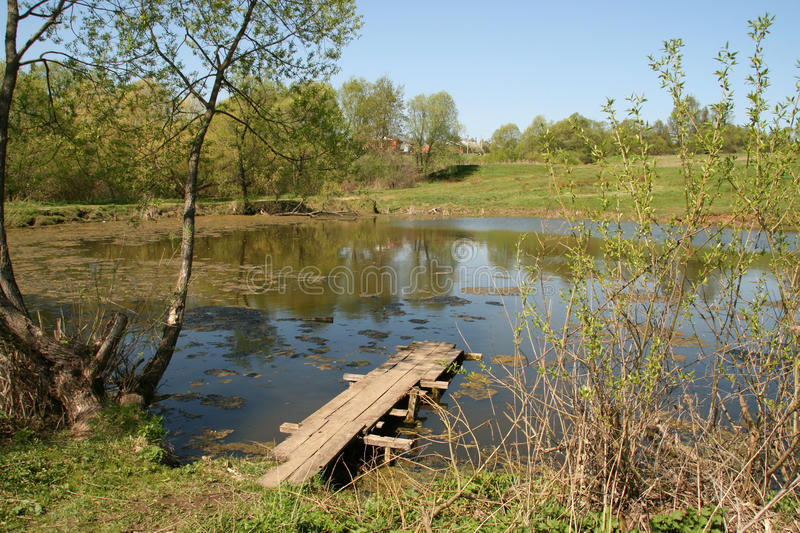 Wooden path on a rural pond stock photo