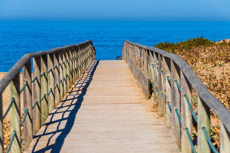 Wooden path on sand to sea. Vacation and rest on a beach concept. Summer, coast, dunes, over, ocean, landscape, water, travel, walkway, nature, boardwalk stock photo