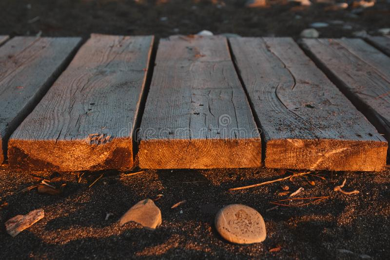 Wooden path on the sandy beach. Beach boardwalk with sand texture background.  stock photo