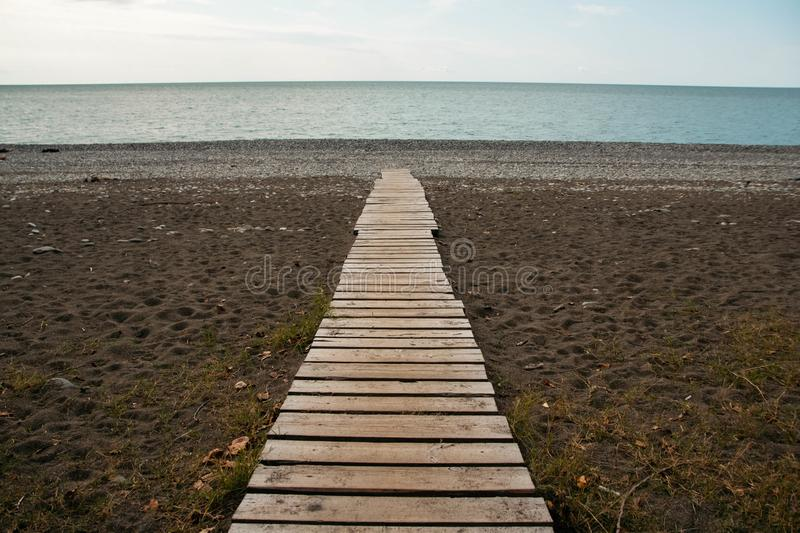 Wooden path on the sandy beach. Beach boardwalk with sand texture background. Wooden path on the sandy beach. Top view. Beach boardwalk with sand texture royalty free stock photography
