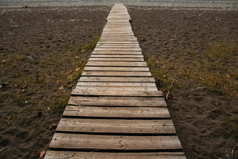 Wooden path on the sandy beach. Beach boardwalk with sand texture background. Wooden path on the sandy beach. Top view. Beach boardwalk with sand texture royalty free stock image