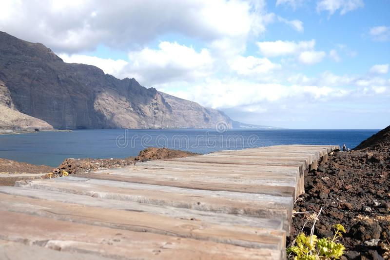 Wooden path to the sea and mountain in the background. Beautiful, summer, landscape, coast, vacation, island, ocean, travel, nature, tourism, beach, blue royalty free stock image