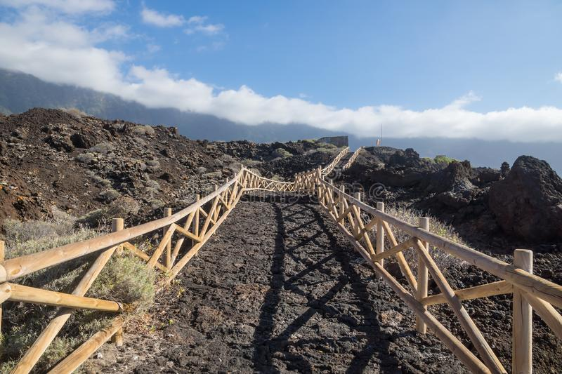 Pathway along the coast with mountaincliff and clouds, El Golfo, Frontera, El Hierro, Canary Islands, Spain. Wooden pathway along the coast with mountaincliff royalty free stock image