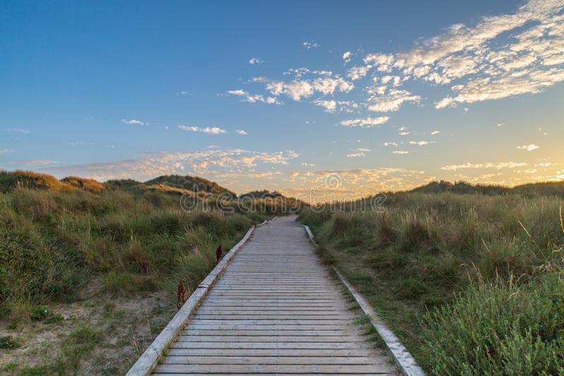 Coastal Pathway. A wooden pathway leading towards the sea at Formby in Merseyside, taken at sunset stock image