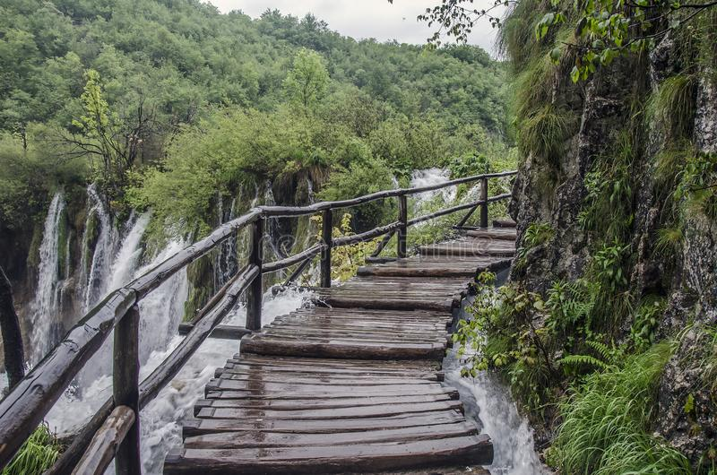 Wooden pathway near big waterfall, Plitvice Lakes National Park, Kroatië stock afbeelding