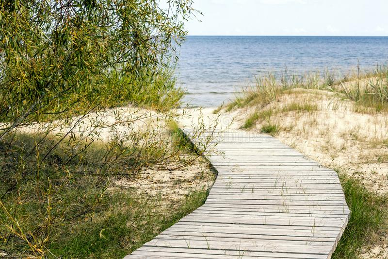 Wooden pathway to the beach on sandy dune. In summer stock image