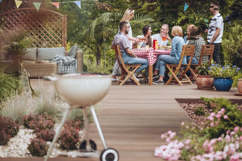 Grill on wooden garden patio. Wooden patio in the garden with a grill standing in the front and happy young people gathered around a table full of food during stock photo