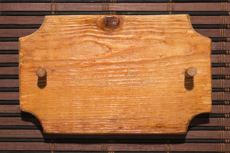 Wooden patterned frame made of wood with a wooden gag is on a bamboo mat. Hard light for hard shadows royalty free stock photography