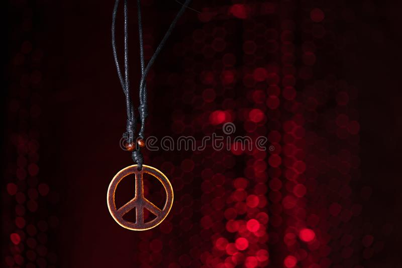 Wooden peace symbol with red lights background stock photos