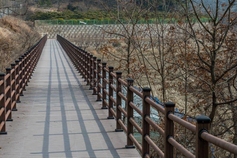 Wooden pedestrian bridge in mountainside park. Wooden pedestrian bridge with shadow of railing in mountainside park on winter day stock images