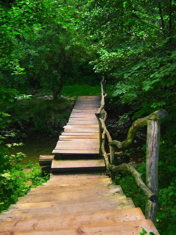 Wooden bridge over a stream in a green forest. Wooden pedestrian bridge over a forest stream stock photos