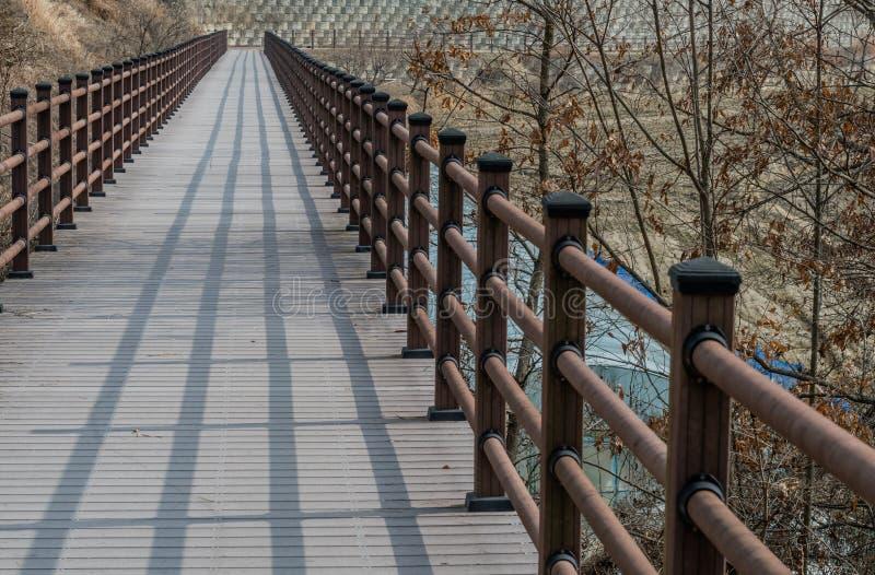Wooden pedestrian bridge in mountainside park. Wooden pedestrian bridge with shadow of railing in mountainside park on winter day royalty free stock photography