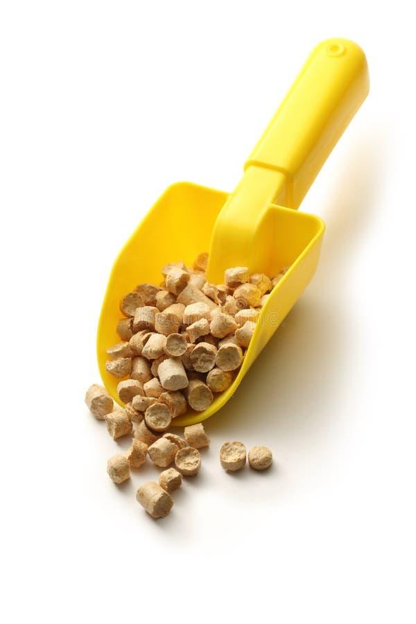 Wooden pellets on plastic shovel royalty free stock image