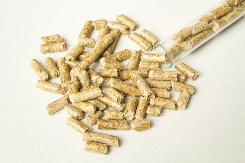Wooden pellets spilled out of the tube. Biomass Pellets - cheap energy. The concept of biofuel production. Alternative background biological burn central chip royalty free stock image
