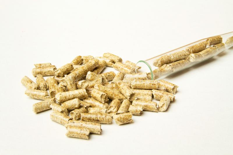 Wooden pellets spilled out of the tube. Biomass Pellets - cheap energy. The concept of biofuel production. Alternative background biological burn central chip royalty free stock photos