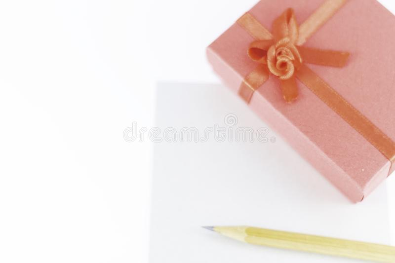 Wooden pencil on empty letter with big red gift box decorated with bow on main plan and white background Valentine`s day. Or festive concept Letter or royalty free stock photos