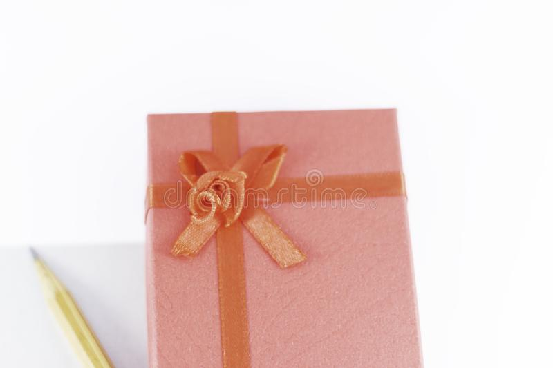 Wooden pencil on empty letter with big red gift box decorated with bow on main plan and white background Valentine`s day. Or festive concept Letter or royalty free stock images