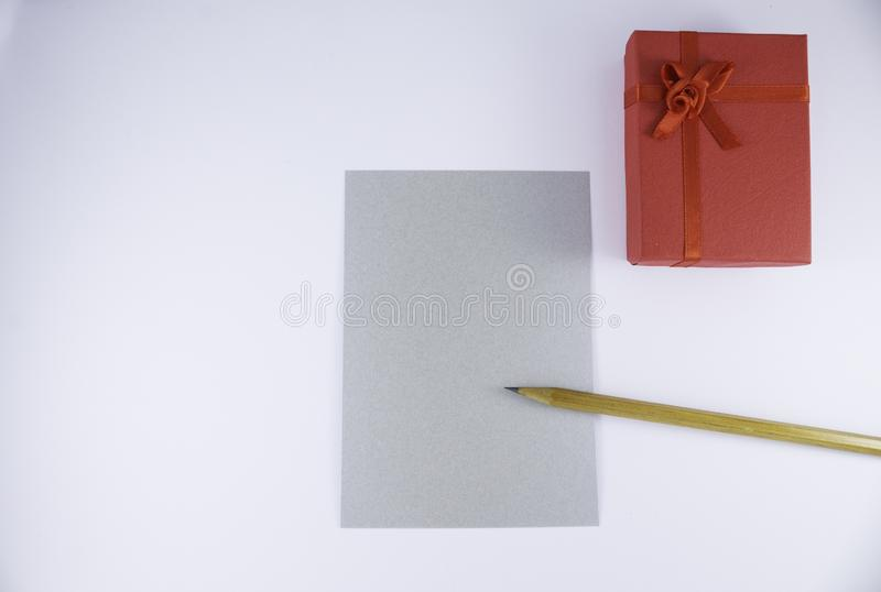 Wooden pencil on empty letter with big red gift box on white background Valentine`s day. Or festive concept Letter or invitation inside Minimalist concept royalty free stock photo