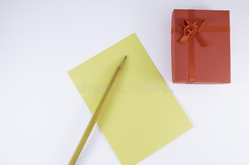 Wooden pencil on empty letter with big red gift box on white background Valentine`s day. Or festive concept Letter or invitation inside Minimalist concept stock image