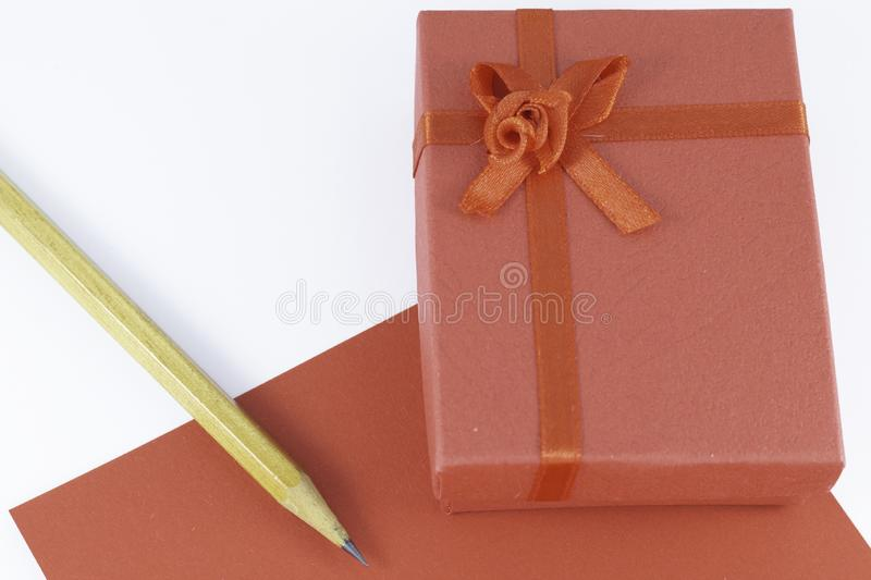 Wooden pencil on empty red letter with big red gift box decorated with bow on main plan and white background Valentine`s day. Or festive concept Letter or stock image
