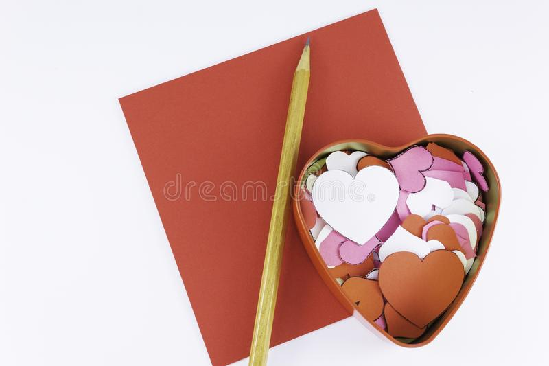 Wooden pencil on an empty red letter near to a box for valentines and different colors inside on a white background Valentine`s. Day or festive concept Letter royalty free stock photography